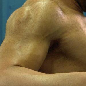 Mies treenaa lihaksiaan salilla.