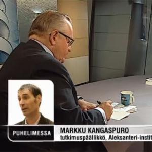 Martti Ahtisaari kirjoittaa studion pöydän ääressä toimittaja Jari Korkkia vastapäätä, pikkukuvassa tutkimuspäällikkö Markku Kangaspuro