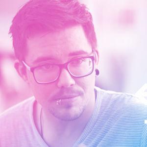 Adam Guarnieri som har mörkt hår, glasögon och piercing i läppen. På bilden står det X3MTRANS.