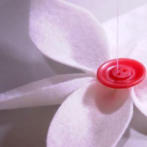 Sy fast en knapp i kronbladens mitt.