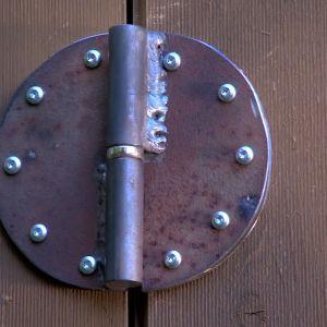 Ett grovt gångjärn på växthusets dörr.