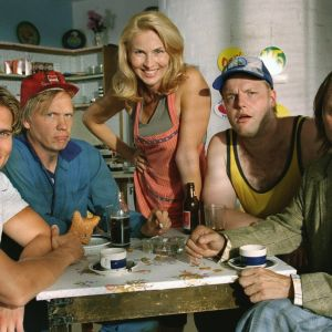Peräkamaripojat-sarjan hahmot pöydän ääressä.