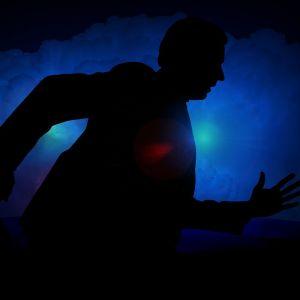 Kuvassa mies juoksee pimeässä salkku kädessä