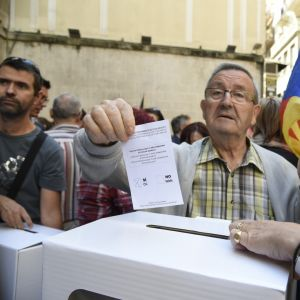 En äldre man sätter en falsk röstsedel i en låda under demonstrationer för Kataloniens självständighet.