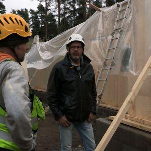 Kaksi miestä keskustelevat rakennustyömaalla