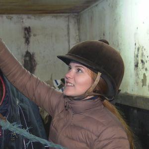 Flicka klappar häst på manen i häststall.