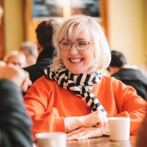 Olga Ketonen istuu pöydän ääressä