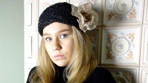 flicka i hatt framför en kakelugn