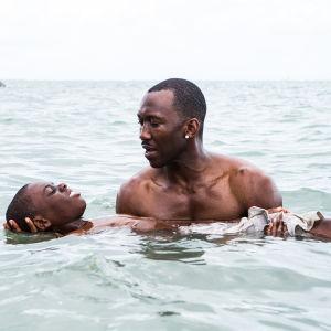 Chiron (Alex R. Hibbert) försöker lära sig att flyta i vattnet medan Juan (Mahershala Ali) håller i honom.