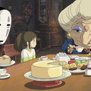 Animaatiokuvassa naamaripäinen hahmo, pieni tyttö ja vanha mummo istuvat pöydän äärellä.
