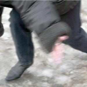 En kvinna faller omkull på en hal trottoar.
