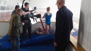 tv-kuvausryhmä kuvaa tyttöä urheiluhallin ylätasanteella Urheilu-Suomi-tv-sarjan imagomainokseen