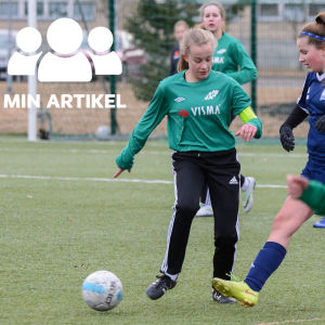 Två tjejer kämpar om bollen på en fotbollsplan. I bakgrunden syns fler fotbollsspelare.
