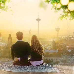 Nainen ja mies istuvan toisiaan vasten kalliolla katsellen surrealistista maisemaa.