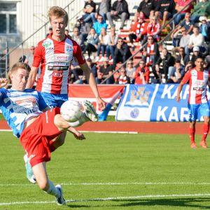 Två fotbollsspelare och en boll på en fotbollsplan