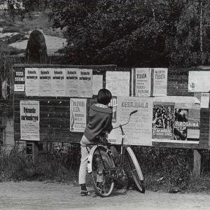 Maaseutu. Tyttö ja polkupyörä ilmoitustaulun edessä v. 1964. Elokuvamainoksia ja ilmoituksia. Kesä.
