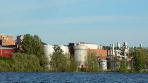 En vy över ett fabriksområde med tegelbyggnader, hallar, silor och skorstenare. Sett från en sjö. Sommar.