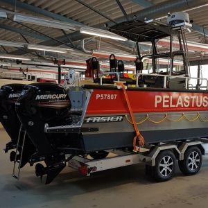 en röd och silverfärgad aluminiumbåt på en trailer inne i en brandstation. Står pelastuslaitos längs båtens långsida. Båten har två utombordsmotorer.