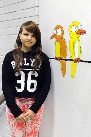 Anastasia Alexandrova, elev i Närpes högstadieskola, står i korridoren framför målning av fåglar