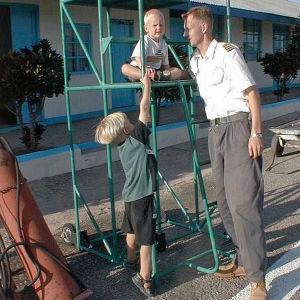 Tansaniassa kaksi suomalaista pikkupoikaa matkalaukkutelineellä leikkimässä. Lentäjä isä seuraa vierestä