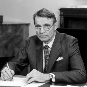 President Mauno Koivisto sitter vid ett bord och undertecknar ett papper.