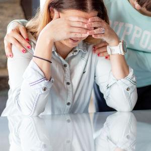 Nainen pitelee päätään käsien välissä. Ystävä tukee ja lohduttaa.