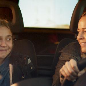 mor och dotter ler mot varandra i framsätet på en bil.