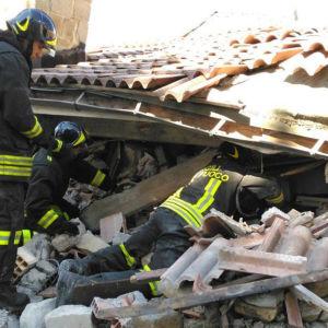 Räddningsarbetare försöker gräva sig in under ett rasat hus i Amatrice.