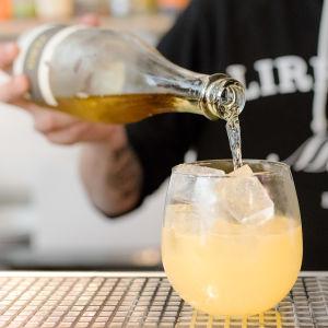 Bar manager Andreas Cederström kaataa keltaiseen drinkkiin alkoholitonta rieslingiä.