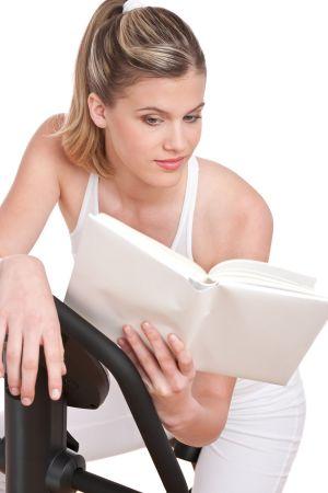 Kuntopyörää käyttävä nainen lukee kirjaa.