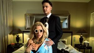 Krista Siegfrids och Roope Salminen poserar i ett hotellrum