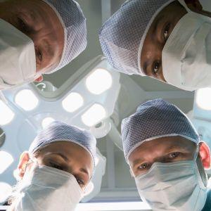 Fyra kirurger som tittar in i kameran ovanifrån.