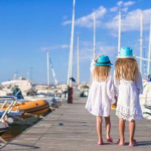 Två flickor i sommarkläder går på båtbrygga i solskenet.