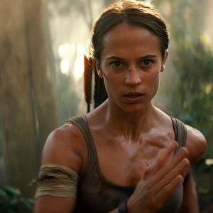 Lara Croft springer rakt mot kameran i djungelmiljö.