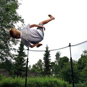 Barn som hoppar i en trampolin.