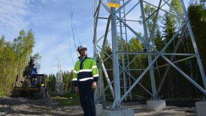 Juha Rintamäki står bredvid en elstolpe i stål i skogen. Han har neongula arbetskläder och hjälm på sig.