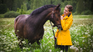 Tumma poni ja keltatakkinen nainen niityllä