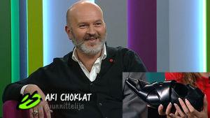 Aki Choklat värikkäässä studiossa ja kuvan alareunassa kuva mustasta kengästä.