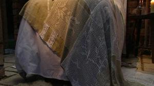 Sängöverkast av virkade gardiner