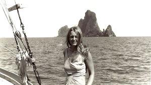 Svartvit bild av Ingrid på en båt med hav i bakgrunden.