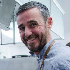 Bagaren Sébastien Boudet tar ut nygräddade bröd ur ugnen.