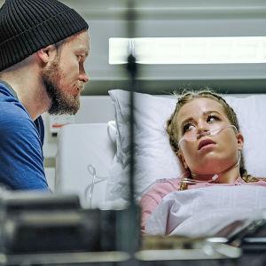 Tyttö makaa sairaalasängyssä happiviiksissä ja katsoo vieressä istuvaa miestä.