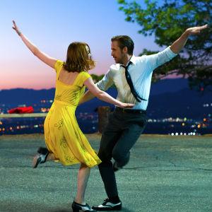 Mia (Emma Stone) och Sebastian (Ryan Gosling) dansar tillsammans på en väg med ett nattligt Los Angeles som fond.