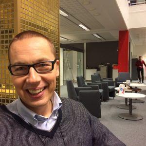 Silmälasipäinen mies nauraa lähikuvassa, taustalla toimiston sohvaryhmä.