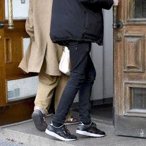 Två pojkar går in genom en dörr.