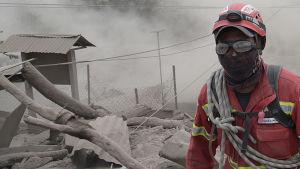 En räddningsarbetare letar efter överlevande i El Rodeo, intill vulkanen Fuego.