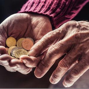 Närbild av händerna på en äldre person med slantar i ena handen