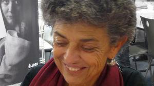 Harmaakiharapäinen nainen hymyilee
