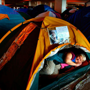 epa000449263 Not long to go now for Cliff Richard fan Pat Denton as she sleeps in her tent Friday 03 June 2005 inside a multi- storey car park at the NIA (National Indoor Arena) in Birmingham, central England. She is among hundreds of fans of the veteran