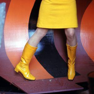 En kvinna poserar i en gul minikjol.